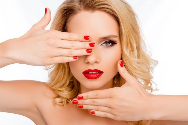 Pretty woman tenendo le mani vicino al viso e mostrando belle palme.