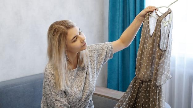 La donna graziosa tiene una gruccia con un vestito e lo guarda. la donna sceglie il vestito a casa