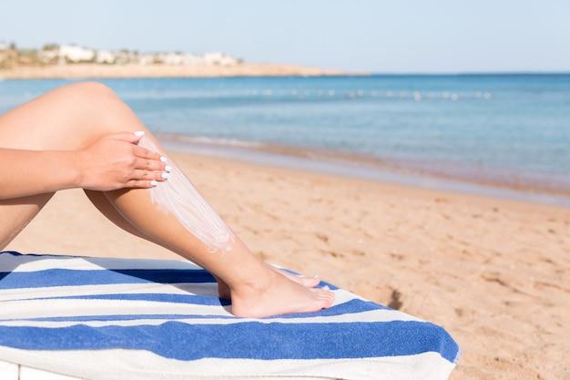 Bella donna sta applicando la crema solare sulla gamba con la mano che si rilassa sul lettino in riva al mare.