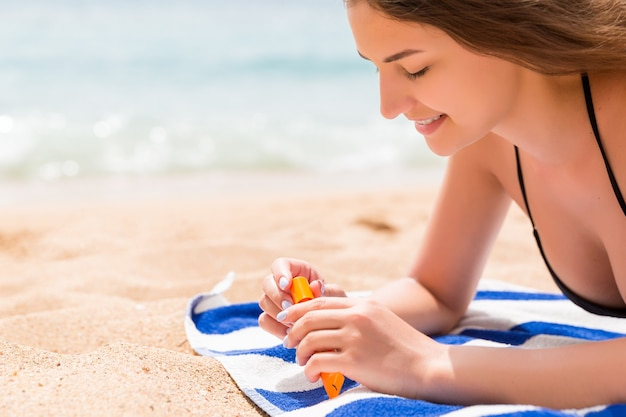 Bella donna è sdraiata sull'asciugamano in spiaggia e apre un tubo di crema solare per proteggere la pelle dalle scottature.