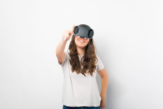 La donna graziosa sta provando i vetri di realtà virtuale sopra fondo bianco.