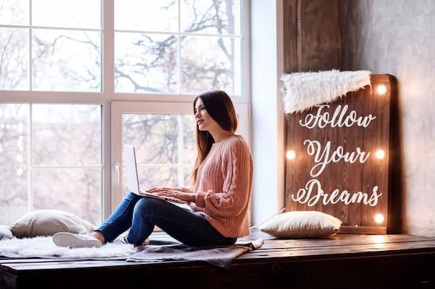 La donna graziosa sta lavorando o studiando a casa. lavoratore a distanza, bogger, insegnante, scrittore, allenatore, studente. segui i tuoi sogni sull'autoisolamento.