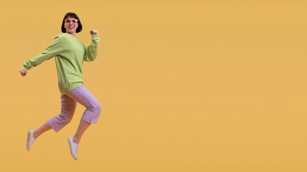 Salto grazioso della donna isolato sull'arancio