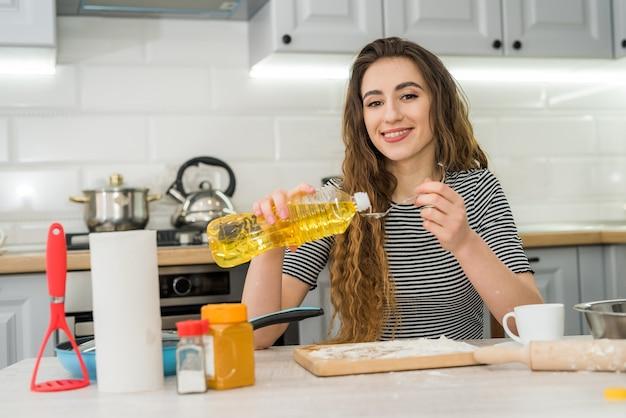 Donna graziosa che impasta la pasta a casa, cucina il cibo per uno stile di vita sano