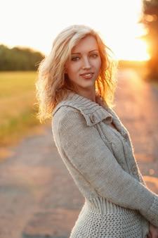 Bella donna in maglione lavorato a maglia al tramonto sulla natura