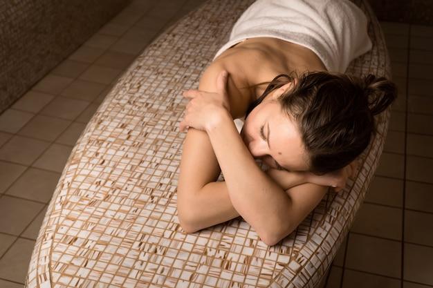Bella donna sdraiata e rilassante nell'hammam nel salone spa