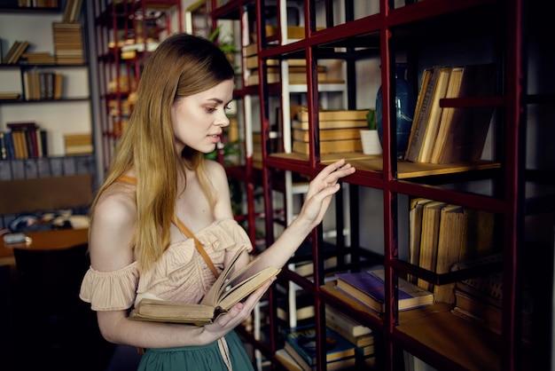 Bella donna in biblioteca alla ricerca di libri e leggendo le vacanze.