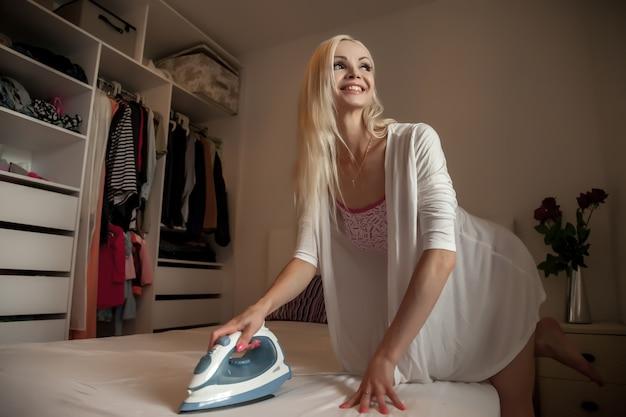 Una donna graziosa, come una bambola, fa i compiti. l'aspetto slavo femminile sorridente stira la biancheria da letto con un ferro da stiro su un grande letto bianco dopo il lavaggio. concetto di comfort domestico o servizi per svolgere il lavoro a casa