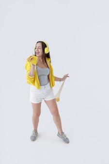 Bella donna che ascolta musica e canta nello smartphone