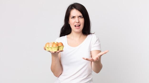 Bella donna che sembra arrabbiata, infastidita e frustrata e con in mano una scatola di uova