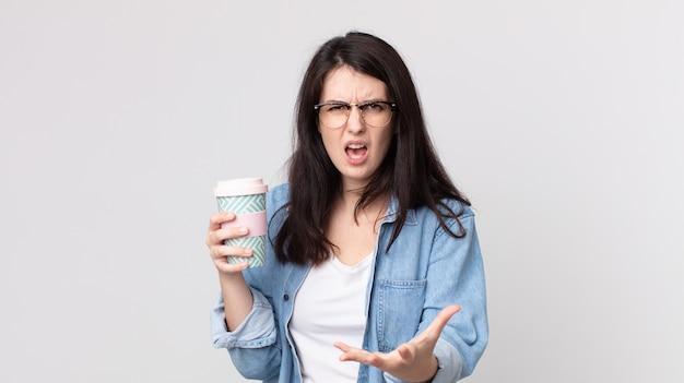 Bella donna che sembra arrabbiata, infastidita e frustrata e con in mano un caffè da asporto