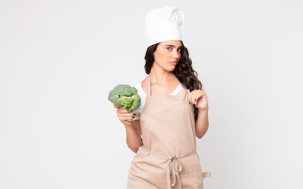 Bella donna che sembra arrogante, di successo, positiva e orgogliosa che indossa un grembiule e tiene in mano un broccolo
