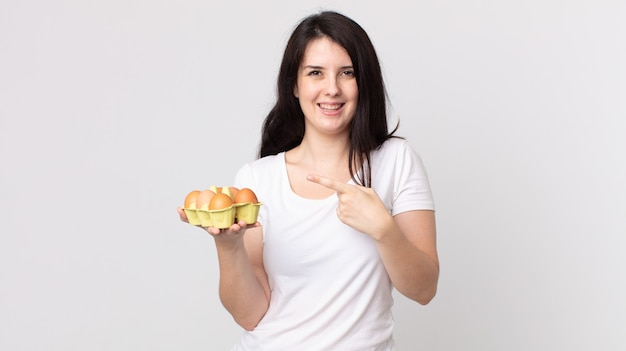 Bella donna che sembra eccitata e sorpresa indicando il lato e tenendo in mano una scatola di uova