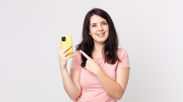 Bella donna che sembra eccitata e sorpresa che indica il lato usando uno smartphone