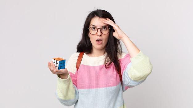Bella donna che sembra felice, stupita e sorpresa e risolve un gioco di intelligenza