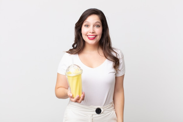 Bella donna che sembra felice e piacevolmente sorpresa e tiene in mano un frullato alla vaniglia