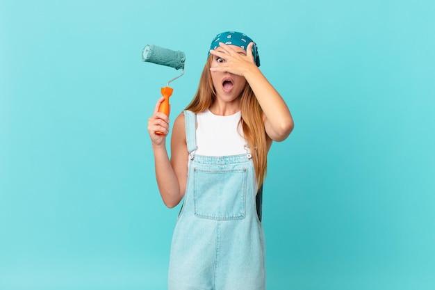 Bella donna che sembra scioccata, spaventata o terrorizzata, coprendo il viso con la pittura a mano di un nuovo muro di casa