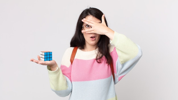 Bella donna che sembra scioccata, spaventata o terrorizzata, coprendo il viso con la mano e risolvendo un gioco di intelligenza