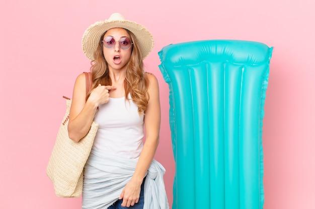 Bella donna che sembra scioccata e sorpresa con la bocca spalancata, che indica se stessa. concetto di estate