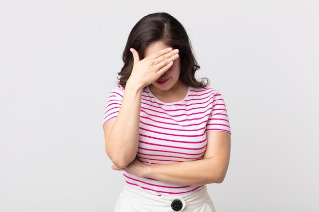 Bella donna che sembra stressata, imbarazzata o turbata, con mal di testa, che copre il viso con la mano