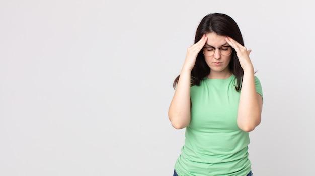 Bella donna che sembra stressata e frustrata, lavora sotto pressione con mal di testa e turbata da problemi