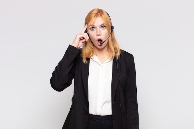 Bella donna che sembra sorpresa, a bocca aperta, scioccata, realizzando un nuovo pensiero, idea o concetto
