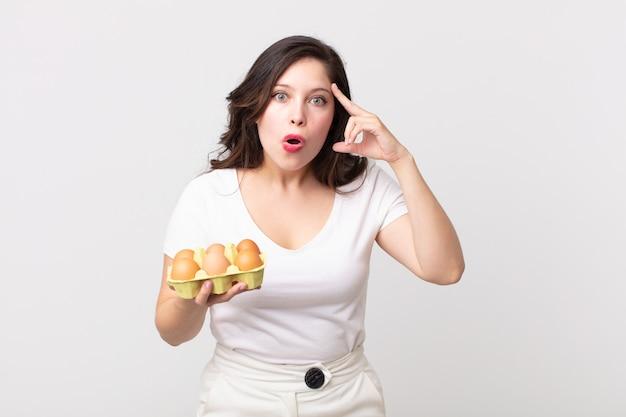 Bella donna che sembra sorpresa, realizzando un nuovo pensiero, idea o concetto e tenendo in mano una scatola di uova