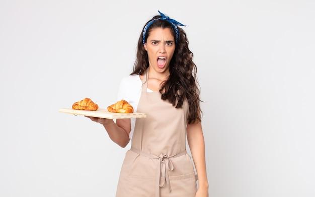 Bella donna che sembra molto scioccata o sorpresa e tiene in mano un vassoio di croissant