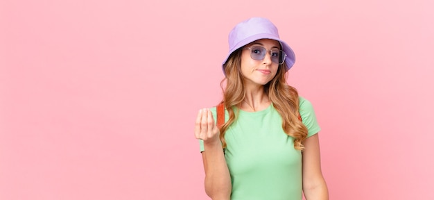 Bella donna che fa un gesto di capice o denaro, dicendoti di pagare. concetto di estate