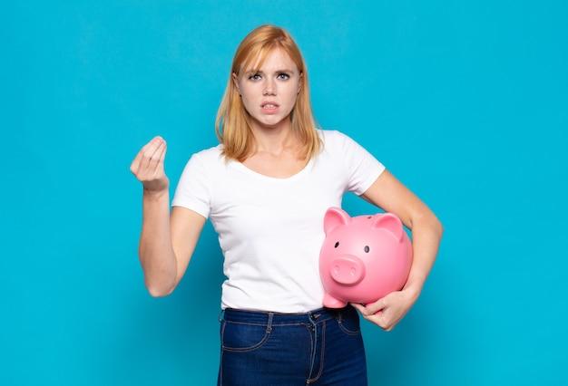 Bella donna che fa un gesto di capice o denaro, dicendoti di pagare i tuoi debiti!