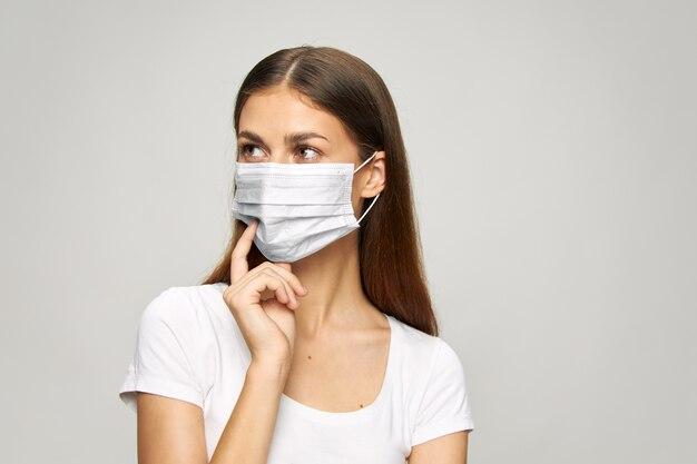 Pretty woman maschera medica sul viso, guarda la sicurezza laterale