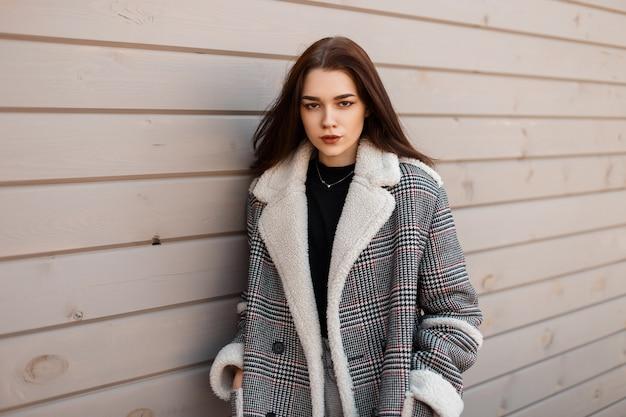 Modello di donna graziosa in giacca di moda sulla strada