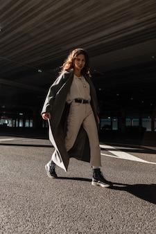 Modello di donna graziosa con capelli ricci in cappotto lungo di moda, maglione bianco, pantaloni e stivali cammina per strada al giorno pieno di sole e ombra. stile e bellezza femminili urbani