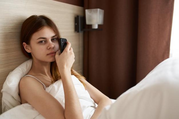 Bella donna al mattino sotto le coperte con un telefono cellulare in mano