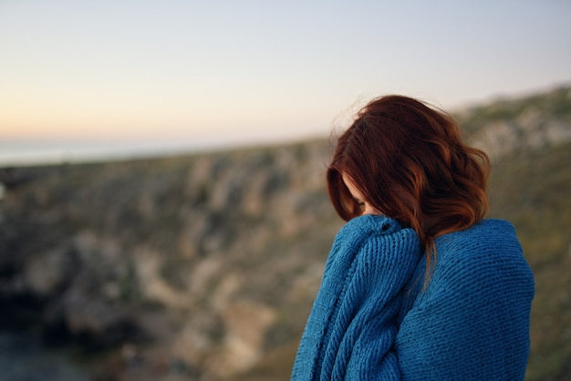 La bella donna in montagna all'aperto si coprì di una coperta fresca in viaggio