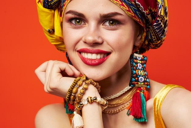 Bella donna in turbante multicolore aspetto attraente gioielli sfondo rosso