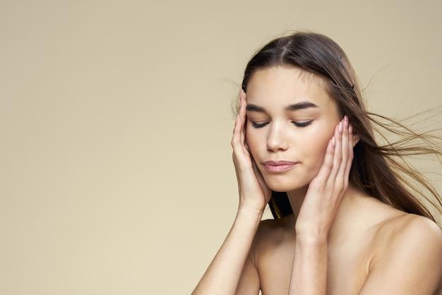Bella donna spalle nude cosmetici pulire la pelle dei capelli cura sfondo beige