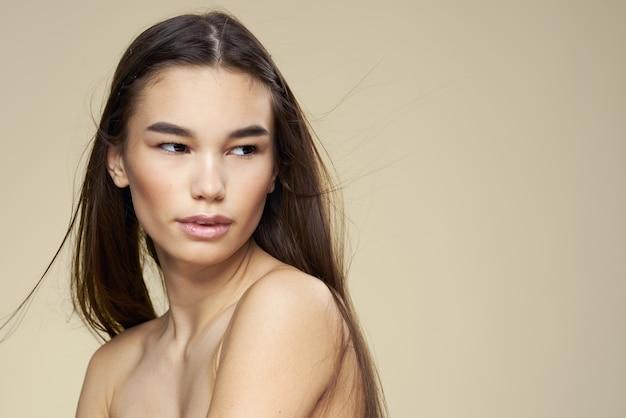 Donna graziosa spalle nude capelli lunghi cura del corpo beige.