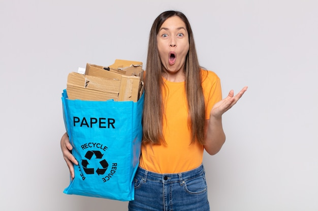 Bella donna a bocca aperta e con in mano un sacchetto di riciclo