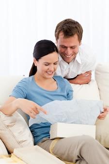Pretty woman aprendo un regalo dal suo fidanzato sul divano