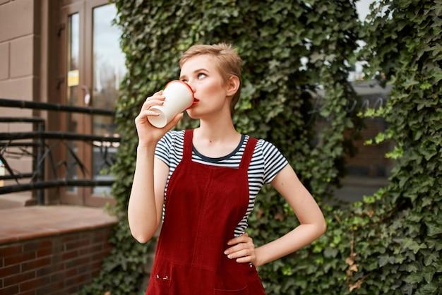 Bella donna all'aperto una tazza di caffè a piedi per il tempo libero coffee