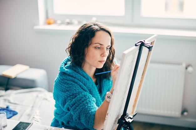 Quadro grazioso della pittura della donna a casa con le pareti bianche, artista femminile concetrata sulla sua opera d'arte