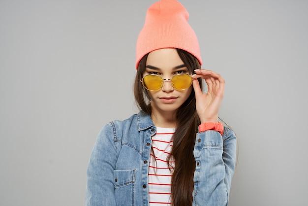 Bella donna in studio di moda occhiali cappello rosa