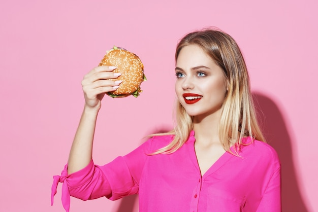 Bella donna in camicia rosa con dieta fast food hamburger