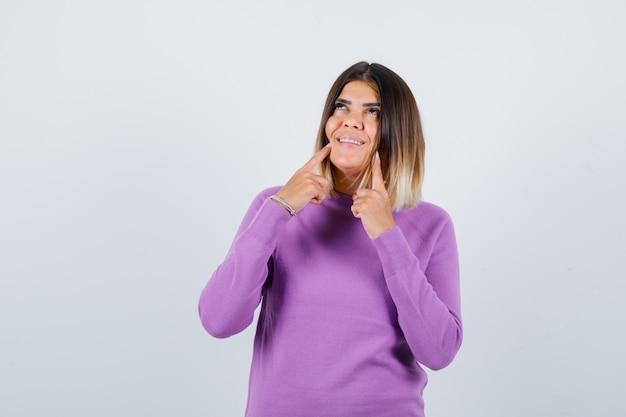 Bella donna che indica le sue fossette, alzando lo sguardo in un maglione viola e guardando allegra, vista frontale.