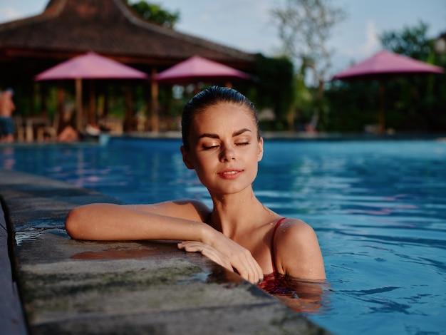 Bella donna in piscina vacanza lusso occhi chiusi natura