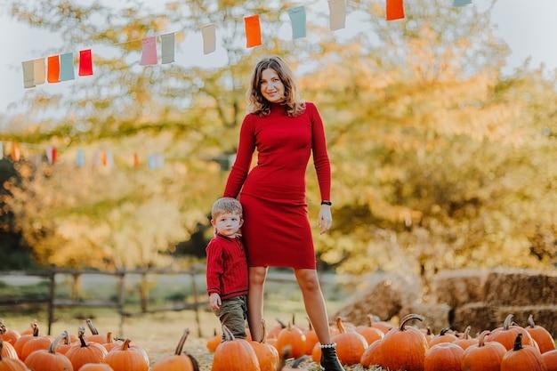 Bella donna in posa con il suo piccolo figlio sul campo di zucca