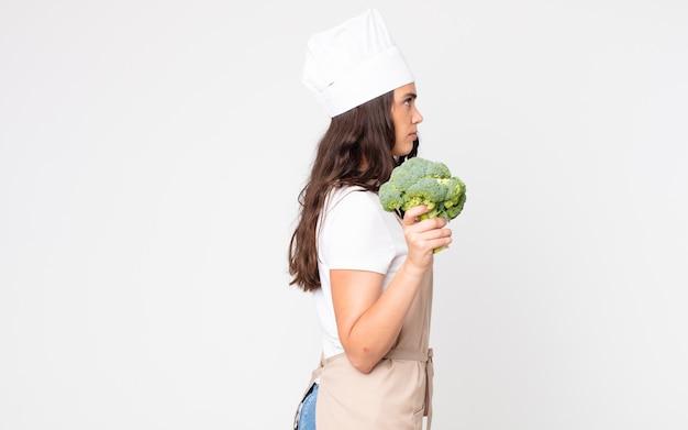 Bella donna sulla vista di profilo che pensa, immagina o sogna ad occhi aperti indossando un grembiule e tenendo in mano un broccolo
