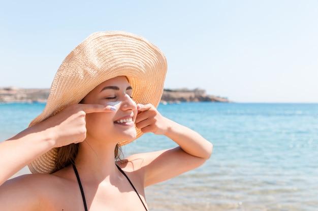 Pretty woman protegge la sua pelle sul viso con crema solare in spiaggia.
