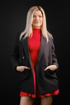 Bella donna in abito rosso e giacca nera in posa in studio scuro